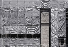 Building covered with wrinkled tarpaulin canvas Stock Image