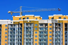 Building crane. Yellow house and building crane Royalty Free Stock Photo