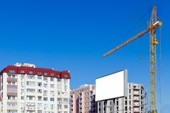 Building crane against the background of a multi-storey building under construction. Advertising billboard with copy space. Royalty Free Stock Images