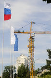 Building Crane And Flags Stock Photo