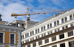 Building crane on the background of city buildings Royalty Free Stock Photos