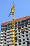 Building crane at the background of a multi-storey building under construction Royalty Free Stock Photography