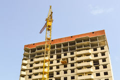 Building crane at the background of a multi-storey building under construction Stock Image