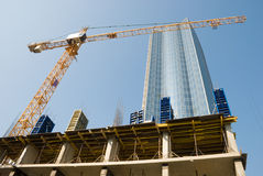 Building crane and building under construction against blue sky Stock Images