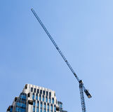 Building crane and construction against blue sky background. Royalty Free Stock Image