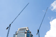 Building crane and construction against blue sky background. Stock Photos