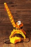 Building crane construction machinery toy on wooden background. Yellow color Royalty Free Stock Photos