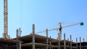 Building crane and construction site under blue sky Stock Photos