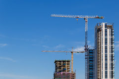 Building crane and construction site under blue sky. Building crane and construction site under blue sky stock photo