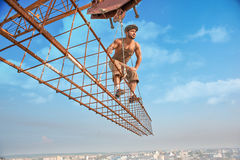 Building crane holding construction with man on high. Royalty Free Stock Images