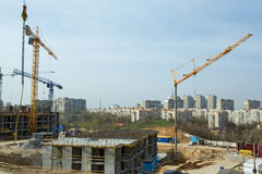 Building crane and houses under construction against blue sky. Tower cranes on the construction of the building. construction site on which to build high-rise Royalty Free Stock Photo