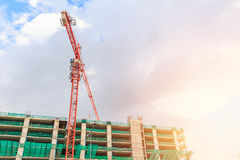 Building with crane with morning sky sun light. Royalty Free Stock Photo