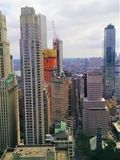Building and crane in nyc 2018. An elevated crane apparatus and skyscrapers of new York city punctuate the overcast sky. Office windows, shiny glass and small royalty free stock photography