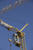 Building crane with steeple cab, blue sky Stock Images