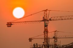 Building and crane under construction. With sunrise or sunset  sky background Stock Photos