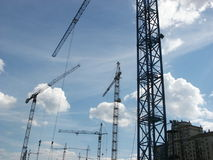 Building cranes. On a background of the blue sky with white clouds and a building Stock Photography