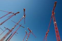 Building Cranes. Many red building cranes rising into a pure blue sky stock photo