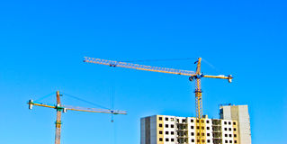 Building cranes above the unfinished apartments. Royalty Free Stock Photo