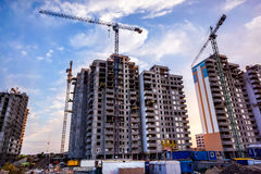 Building cranes at the background of a multi-storey building under construction. Two building cranes at the background of a multi-storey building under stock image