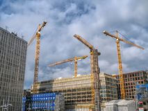 Building cranes building new building construction on the cloudy background. Building cranes building new building construction on the blue cloudy background royalty free stock photography