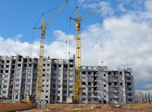 Building cranes and building under construction. On blue sky background. Urban high rise landscape Royalty Free Stock Images