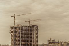 Building cranes and building under construction stylized photo. Building cranes and building under construction stylized photo Royalty Free Stock Images