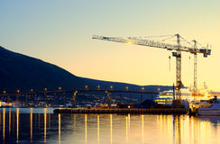 Building cranes in evening Tromso background Stock Photography