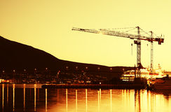 Building cranes in evening Tromso background Stock Photos