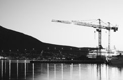 Building cranes in evening Tromso background Royalty Free Stock Images