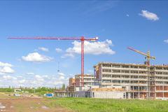 Building and cranes under construction against blue sky Stock Photos