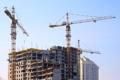 Building cranes and under construction building. Against the clear sky Royalty Free Stock Photo