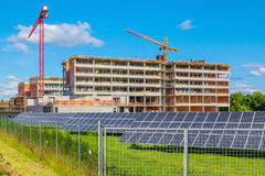 Building and cranes under construction with solar panels Royalty Free Stock Images