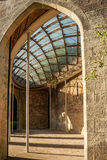 Building With Cross Hatched Ceiling. The interior of a stone brick building with a patterned glass ceiling stock photo
