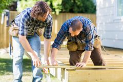 Building a Deck. Mid adult carpenter marking wood while building deck Royalty Free Stock Photography