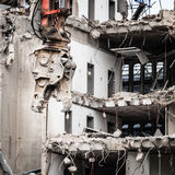 Building demolition by machinery for new construction. Urban scene. Dismantling of a house. Building demolition and crashing by machinery for new construction Stock Photo