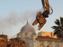 Building demolition shear. Looks like godzilla, looks like eating a dome of a building stock photos