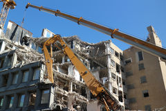 Building demolition. Demolition of building structure with heavy machines and cranes Royalty Free Stock Photos