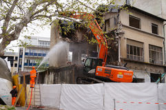 Building Demolition by workers in orange uniform , Switzerland Royalty Free Stock Photo
