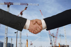 Building developers. Two men shaking hands in front of a major construction site Royalty Free Stock Photo