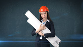 Building, developing, consrtuction and architecture concept -businesswoman in orange helmet with blueprint. Stock Photography
