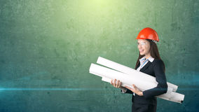 Building, developing, consrtuction and architecture concept -businesswoman in orange helmet, glasses with blueprint. Stock Images