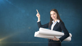 Building, developing, consrtuction and architecture concept - smiling beautiful businesswoman in suit with blueprint Stock Photography