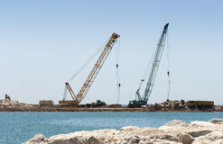 Building a dike. Cranes and excavator put stones Stock Photography
