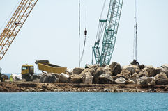 Building a dike. Cranes and excavator put stones Royalty Free Stock Image