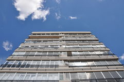 The building is directed to the sky. Multi-storey building. The building is directed to the sky. A multi-storey building against a blue sky with white clouds Stock Images