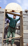 Building a door arch. A senior builder constructing an arch above a door in a newly constructed house Royalty Free Stock Photo