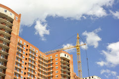 Building with elevating crane Stock Image