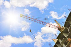 Building with elevating crane and sky with sun Stock Images
