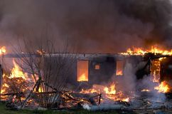 Building Engulfed In Flames. An old building fire. Fire department practice burn or controlled burn Stock Photography