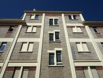 Grey brick building soars into blue sky. Building façade made of grey bricks soars into blue sky in Paris, France royalty free stock photo